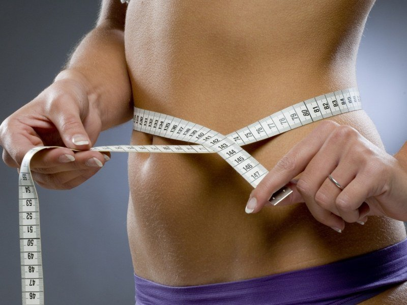 Девушка измеряет талию сантиметровой лентой
