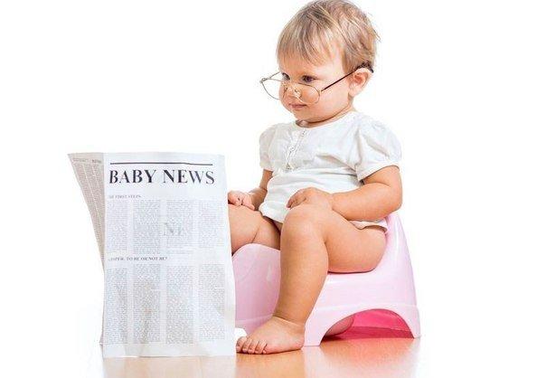 Девочка на розовом горшке читает газету
