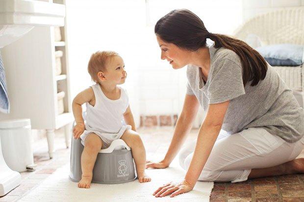 Мама наклонилась к малышу в белой майке, сидящему на сером горшке