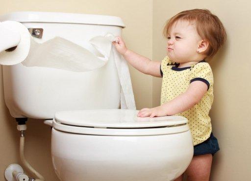 Годовалая девочка разматывает туалетную бумагу рядом с унитазом
