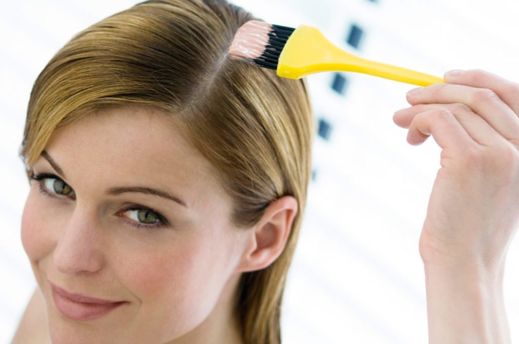 Девушка наносит маску для волос специальной кистью